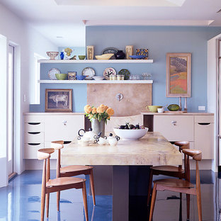 This is an example of a modern eat-in kitchen in Baltimore with flat-panel cabinets, beige cabinets, marble benchtops, blue splashback, concrete floors, with island and blue floor.