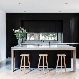 Пример оригинального дизайна: параллельная кухня в современном стиле с врезной раковиной, плоскими фасадами, черными фасадами, фартуком с окном, техникой под мебельный фасад, островом, бежевым полом и серой столешницей