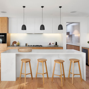 This is an example of a large contemporary l-shaped open plan kitchen in Melbourne with an undermount sink, flat-panel cabinets, medium wood cabinets, black appliances, medium hardwood floors, with island, brown floor, white benchtop, quartz benchtops and white splashback.
