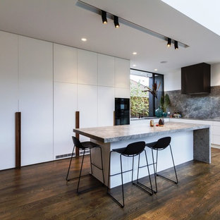 Large modern l-shaped open plan kitchen in Melbourne with an undermount sink, flat-panel cabinets, white cabinets, grey splashback, marble splashback, with island, brown floor, grey benchtop, panelled appliances, dark hardwood floors and limestone benchtops.