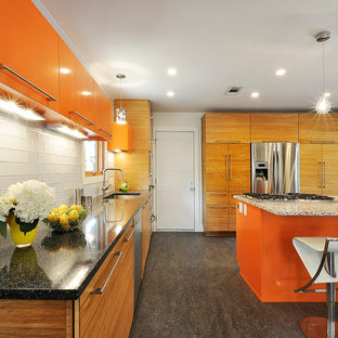 Inspiration for an eclectic kitchen in Austin with an undermount sink, flat-panel cabinets, orange cabinets, white splashback, glass tile splashback and stainless steel appliances.