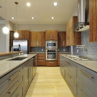 オースティンのコンテンポラリースタイルのおしゃれなキッチン (アンダーカウンターシンク、フラットパネル扉のキャビネット、中間色木目調キャビネット、グレーのキッチンパネル、サブウェイタイルのキッチンパネル、シルバーの調理設備の) の写真
