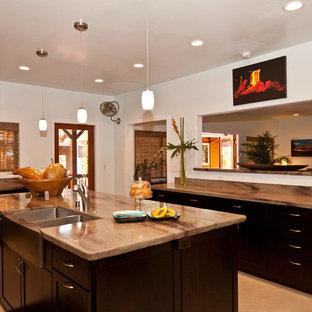 Kolonialstil Küche mit Doppelwaschbecken, flächenbündigen Schrankfronten, dunklen Holzschränken, Porzellan-Bodenfliesen und Kücheninsel in Hawaii