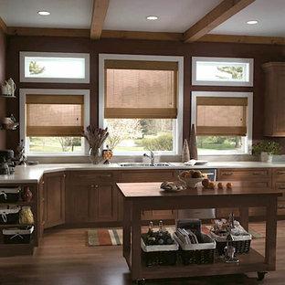 シャーロットの大きいカントリー風おしゃれなキッチン (ドロップインシンク、落し込みパネル扉のキャビネット、中間色木目調キャビネット、シルバーの調理設備の、無垢フローリング、茶色い床、ベージュのキッチンカウンター) の写真