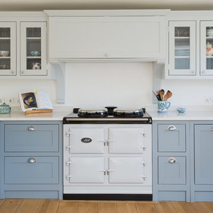 Photo of a medium sized country kitchen/diner in Gloucestershire with shaker cabinets, blue cabinets, quartz worktops, light hardwood flooring and no island.