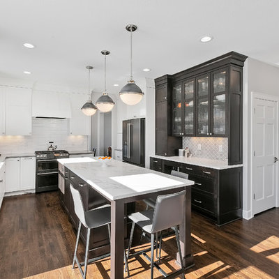 Eat-in kitchen - mid-sized transitional u-shaped brown floor and dark wood floor eat-in kitchen idea in Minneapolis with a farmhouse sink, white backsplash, an island, white countertops, recessed-panel cabinets, white cabinets, quartzite countertops, subway tile backsplash and stainless steel appliances