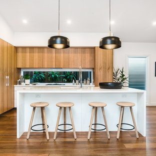 This is an example of a contemporary l-shaped kitchen in Gold Coast - Tweed with an undermount sink, flat-panel cabinets, medium wood cabinets, window splashback, stainless steel appliances, medium hardwood floors, with island and brown floor.