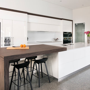 This is an example of a contemporary galley kitchen in Perth with a double-bowl sink, flat-panel cabinets, white cabinets, white splashback, panelled appliances, with island, grey floor and white benchtop.