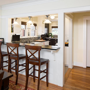 This is an example of a medium sized classic u-shaped kitchen pantry in San Diego with a belfast sink, recessed-panel cabinets, white cabinets, soapstone worktops, black splashback, stone tiled splashback, stainless steel appliances and travertine flooring.