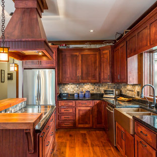Photo of an arts and crafts u-shaped separate kitchen in Other with a drop-in sink, dark wood cabinets, granite benchtops, multi-coloured splashback, terra-cotta splashback and stainless steel appliances.