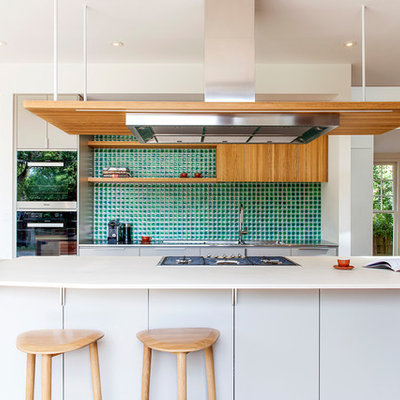 Kitchen - contemporary galley medium tone wood floor and orange floor kitchen idea in Melbourne with flat-panel cabinets, white cabinets, green backsplash, stainless steel appliances and an island