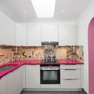 На фото: угловая кухня среднего размера в стиле фьюжн с плоскими фасадами, техникой из нержавеющей стали, серым полом, белыми фасадами, разноцветным фартуком и розовой столешницей с
