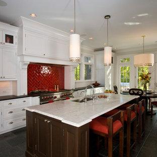 Große, Einzeilige Klassische Wohnküche mit Unterbauwaschbecken, Schrankfronten mit vertiefter Füllung, weißen Schränken, Marmor-Arbeitsplatte, Küchenrückwand in Rot, Rückwand aus Porzellanfliesen, Schieferboden, Kücheninsel und schwarzem Boden in Chicago