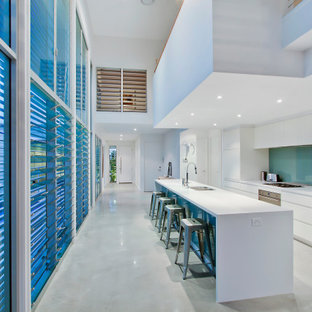 Design ideas for a contemporary galley kitchen in Gold Coast - Tweed with an undermount sink, flat-panel cabinets, white cabinets, blue splashback, glass sheet splashback, stainless steel appliances, with island, grey floor and white benchtop.