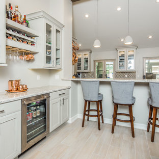 This is an example of a mid-sized transitional galley eat-in kitchen in San Diego with an undermount sink, shaker cabinets, beige cabinets, granite benchtops, beige splashback, porcelain splashback, stainless steel appliances, light hardwood floors and beige floor.