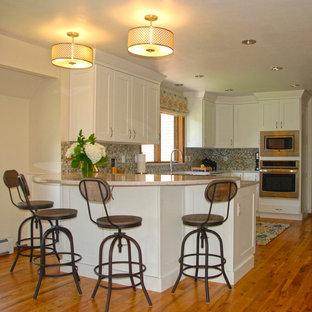 オマハの小さいビーチスタイルのおしゃれなキッチン (シェーカースタイル扉のキャビネット、白いキャビネット、クオーツストーンカウンター、マルチカラーのキッチンパネル、ガラスタイルのキッチンパネル、シルバーの調理設備の、無垢フローリング、オレンジの床、グレーのキッチンカウンター、エプロンフロントシンク) の写真