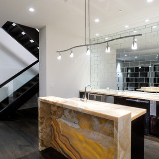 This is an example of a contemporary kitchen in Denver with mirror splashback and onyx benchtops.