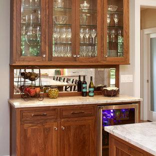 Große Klassische Küche in U-Form mit Schrankfronten mit vertiefter Füllung, hellbraunen Holzschränken, Marmor-Arbeitsplatte, Rückwand aus Spiegelfliesen, Küchengeräten aus Edelstahl, hellem Holzboden und Kücheninsel in New York