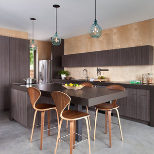 Photo of a mid-sized contemporary galley eat-in kitchen in Austin with flat-panel cabinets, laminate benchtops, stainless steel appliances, concrete floors, an island, a single-bowl sink, dark wood cabinets, brown splashback, timber splashback and grey floor.