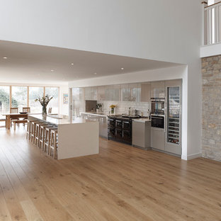 Photo of an expansive modern single-wall open plan kitchen in Other with an integrated sink, flat-panel cabinets, grey cabinets, solid surface benchtops, white splashback, ceramic splashback, stainless steel appliances, light hardwood floors and with island.
