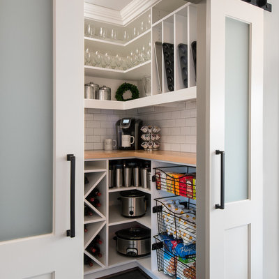Example of a small transitional dark wood floor and brown floor kitchen pantry design in Detroit with white cabinets, white backsplash, subway tile backsplash, stainless steel appliances, a farmhouse sink, wood countertops, white countertops and open cabinets