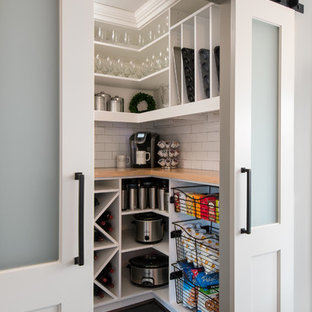 Small transitional kitchen pantry inspiration - Example of a small transitional l-shaped dark wood floor and brown floor kitchen pantry design in Detroit with shaker cabinets, white cabinets, white backsplash, subway tile backsplash, stainless steel appliances, an island, a farmhouse sink, wood countertops and white countertops