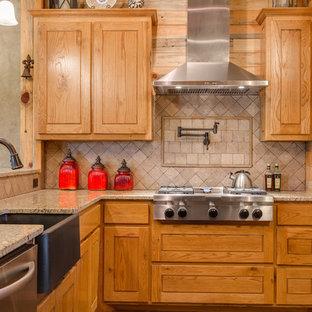 Offene, Mittelgroße Rustikale Küche ohne Insel in L-Form mit Landhausspüle, profilierten Schrankfronten, hellen Holzschränken, Granit-Arbeitsplatte, Küchenrückwand in Beige, Rückwand aus Travertin, Küchengeräten aus Edelstahl, Betonboden und braunem Boden in Dallas