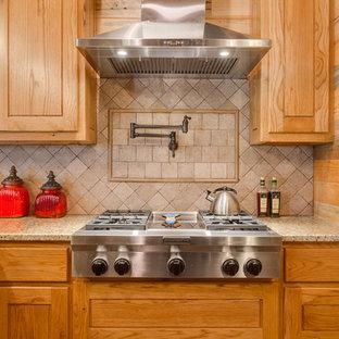 Offene, Mittelgroße Urige Küche ohne Insel in L-Form mit Landhausspüle, profilierten Schrankfronten, hellen Holzschränken, Granit-Arbeitsplatte, Küchenrückwand in Beige, Rückwand aus Travertin, Küchengeräten aus Edelstahl, Betonboden und braunem Boden in Dallas
