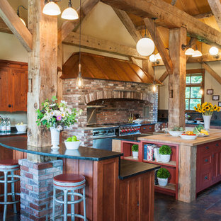 Design ideas for a rural u-shaped kitchen in Other with dark wood cabinets, grey splashback, stainless steel appliances, an island and brown floors.