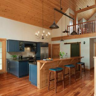 Cette photo montre une cuisine américaine linéaire nature de taille moyenne avec un placard à porte shaker, des portes de placard bleues, un électroménager en acier inoxydable, un sol en bois brun, un îlot central, un sol marron, un plan de travail en surface solide, un plan de travail noir et une crédence beige.