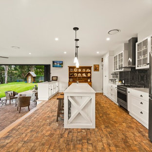 Photo of a country galley open plan kitchen in Other with shaker cabinets, white cabinets, black splashback, stainless steel appliances, brick floors, with island, brown floor and white benchtop.
