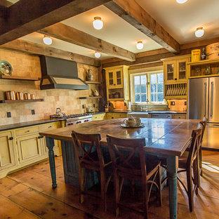 Country Küche in L-Form mit Landhausspüle, Schrankfronten mit vertiefter Füllung, gelben Schränken, Marmor-Arbeitsplatte, Küchenrückwand in Beige, Rückwand aus Travertin, Küchengeräten aus Edelstahl, braunem Holzboden und Kücheninsel in Sonstige