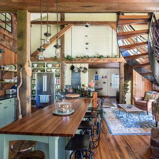 Offene, Große Rustikale Küche mit Unterbauwaschbecken, grünen Schränken, Speckstein-Arbeitsplatte, Küchengeräten aus Edelstahl, braunem Holzboden, Kücheninsel, schwarzer Arbeitsplatte, Schrankfronten im Shaker-Stil und Rückwand aus Holz in Boston