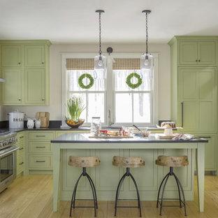バーリントンのカントリー風おしゃれなキッチン (シェーカースタイル扉のキャビネット、緑のキャビネット、シルバーの調理設備、無垢フローリング、茶色い床、黒いキッチンカウンター) の写真