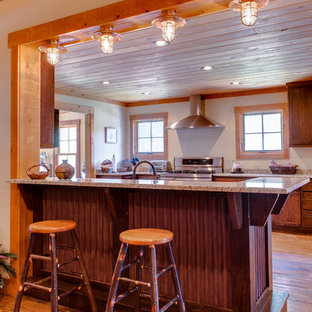 Design ideas for a mid-sized country u-shaped eat-in kitchen in Other with louvered cabinets, dark wood cabinets, granite benchtops, beige splashback, stainless steel appliances, light hardwood floors and a peninsula.