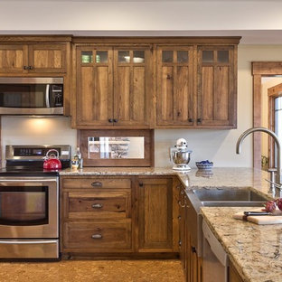 Новые идеи обустройства дома: п-образная кухня среднего размера в стиле кантри с обеденным столом, раковиной в стиле кантри, фасадами в стиле шейкер, темными деревянными фасадами, столешницей из гранита, техникой из нержавеющей стали, пробковым полом, полуостровом и коричневым полом