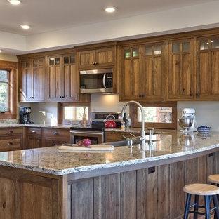 Стильный дизайн: п-образная кухня среднего размера в стиле кантри с обеденным столом, раковиной в стиле кантри, фасадами в стиле шейкер, темными деревянными фасадами, гранитной столешницей, техникой из нержавеющей стали, пробковым полом, полуостровом и коричневым полом - последний тренд