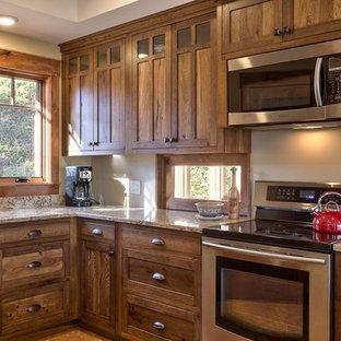 Inredning av ett amerikanskt mellanstort kök, med skåp i shakerstil, skåp i mörkt trä, granitbänkskiva och rostfria vitvaror