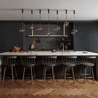 Photo of a large contemporary single-wall kitchen/diner in London with black cabinets, marble worktops, an island, a submerged sink, flat-panel cabinets, beige splashback, integrated appliances, medium hardwood flooring, brown floors and white worktops.