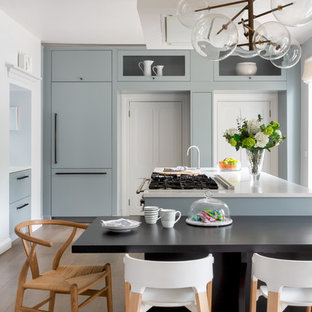 Traditional kitchen/diner in London with a double-bowl sink, flat-panel cabinets, blue cabinets, composite countertops, mirror splashback, stainless steel appliances, medium hardwood flooring, a breakfast bar, brown floors and white worktops.