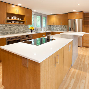 Design ideas for a mid-sized midcentury u-shaped kitchen in Milwaukee with an undermount sink, flat-panel cabinets, medium wood cabinets, quartz benchtops, black splashback, porcelain splashback, stainless steel appliances, vinyl floors and with island.