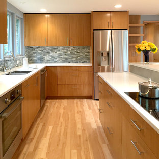 Mid-sized midcentury u-shaped kitchen in Milwaukee with an undermount sink, flat-panel cabinets, medium wood cabinets, quartz benchtops, porcelain splashback, stainless steel appliances, vinyl floors, with island and grey splashback.