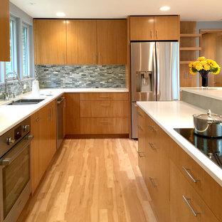 Mid-sized midcentury u-shaped kitchen in Milwaukee with an undermount sink, flat-panel cabinets, medium wood cabinets, quartz benchtops, porcelain splashback, stainless steel appliances, vinyl floors, with island and grey splashback.