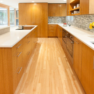 This is an example of a mid-sized midcentury u-shaped kitchen in Milwaukee with an undermount sink, flat-panel cabinets, medium wood cabinets, quartz benchtops, black splashback, glass tile splashback, stainless steel appliances, vinyl floors and with island.