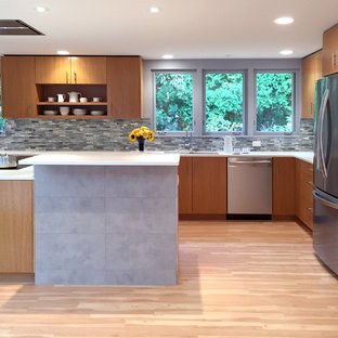 This is an example of a mid-sized midcentury u-shaped kitchen in Milwaukee with a double-bowl sink, open cabinets, medium wood cabinets, quartz benchtops, grey splashback, glass tile splashback, stainless steel appliances, vinyl floors and with island.