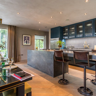Inspiration for a medium sized urban single-wall open plan kitchen in London with glass-front cabinets, concrete worktops, grey splashback, stainless steel appliances, light hardwood flooring, an island and beige floors.