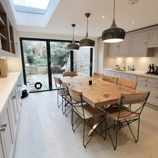 Einzeilige, Mittelgroße Moderne Wohnküche ohne Insel mit Einbauwaschbecken, Schrankfronten im Shaker-Stil, lila Schränken, Mineralwerkstoff-Arbeitsplatte, Küchenrückwand in Weiß, Küchengeräten aus Edelstahl, braunem Holzboden, braunem Boden und weißer Arbeitsplatte in London