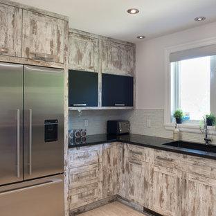 モントリオールの大きいシャビーシック調のおしゃれなキッチン (アンダーカウンターシンク、シェーカースタイル扉のキャビネット、ヴィンテージ仕上げキャビネット、珪岩カウンター、グレーのキッチンパネル、ボーダータイルのキッチンパネル、シルバーの調理設備、淡色無垢フローリング、アイランドなし、ベージュの床、黒いキッチンカウンター) の写真