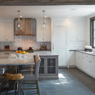 Inspiration for a mid-sized country eat-in kitchen in Chicago with a drop-in sink, recessed-panel cabinets, white cabinets, marble benchtops, white splashback, ceramic splashback, stainless steel appliances, porcelain floors, multiple islands and brown floor.