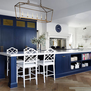 This is an example of a transitional kitchen in Melbourne with shaker cabinets, blue cabinets, white splashback, light hardwood floors, with island and white benchtop.